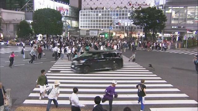 東京の渋谷 大勢の人がいるスクランブル交差点に車