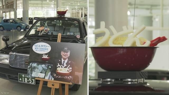 タクシーがまちの有名な食べ物の飾りを付けて走る