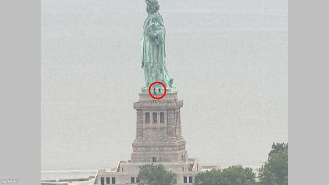 アメリカの「自由の女神像」に登った女を警察が捕まえる